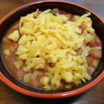 Bowl of pintos with shredded cheddar cheese
